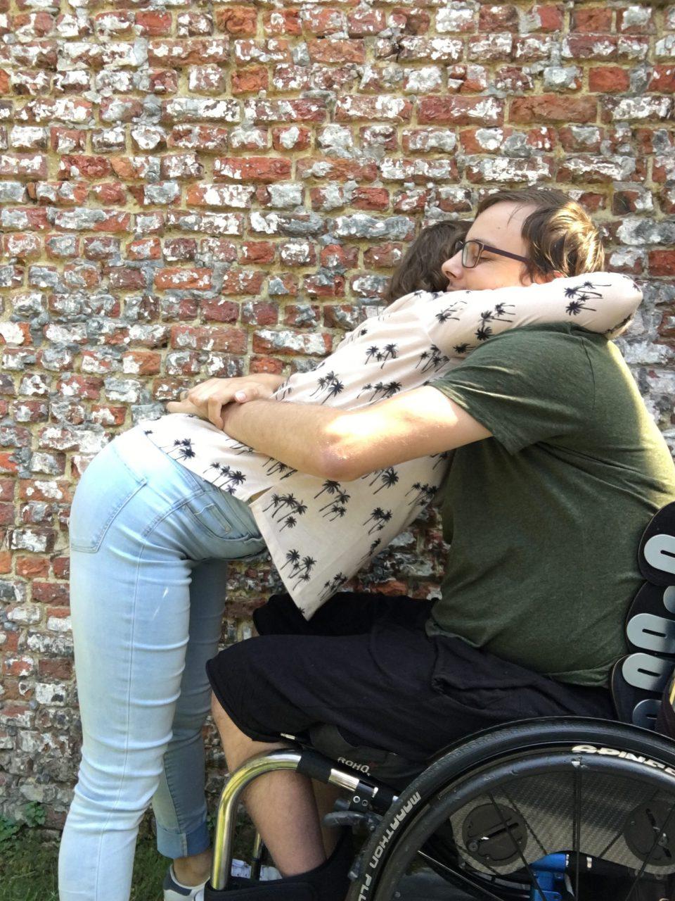 een knuffel met iemand in een rolstoel